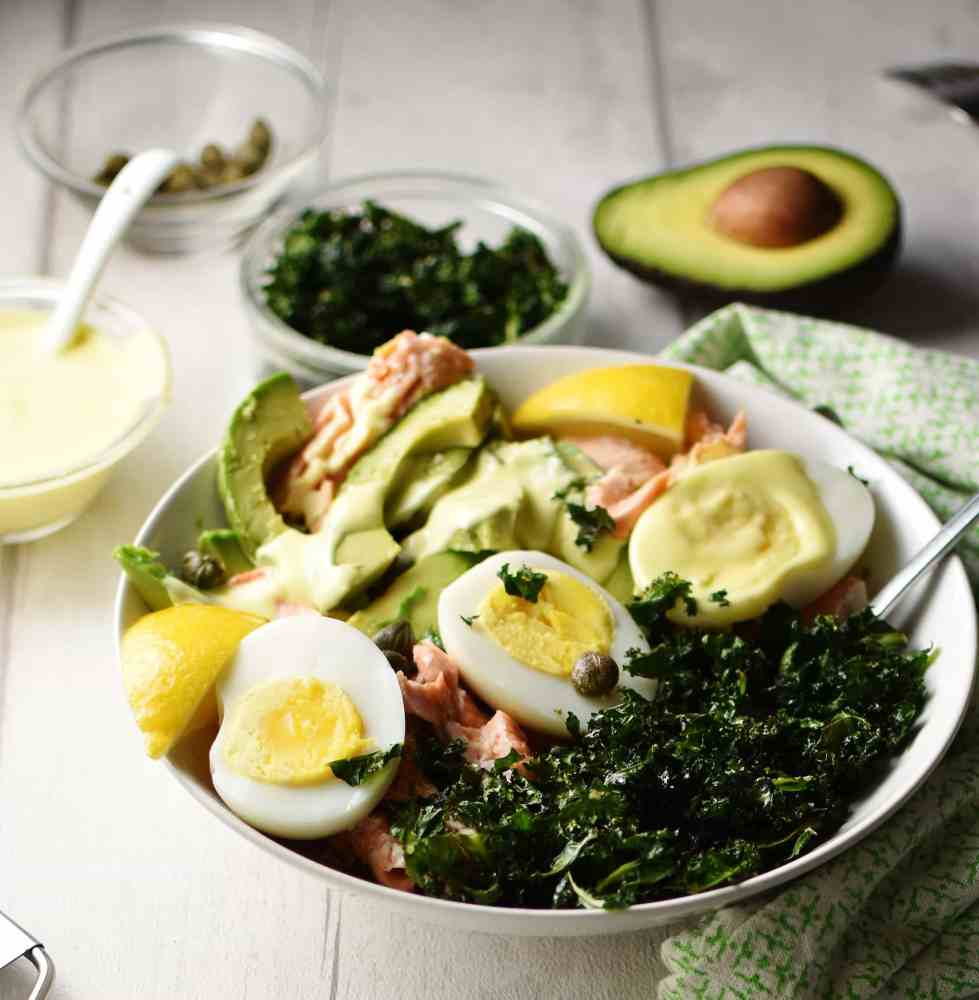 Salmon and avocado salad with crispy kale, egg halves and lemon wedges in white bowl, with avocado half, green cloth, crispy kale, and salad dressing in separate dishes in background