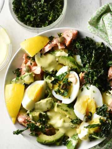 Top down view of salmon and avocado salad with kale, eggs and lemon wedges in white bowl, and salad dressing, crispy kale and green cloth in background.