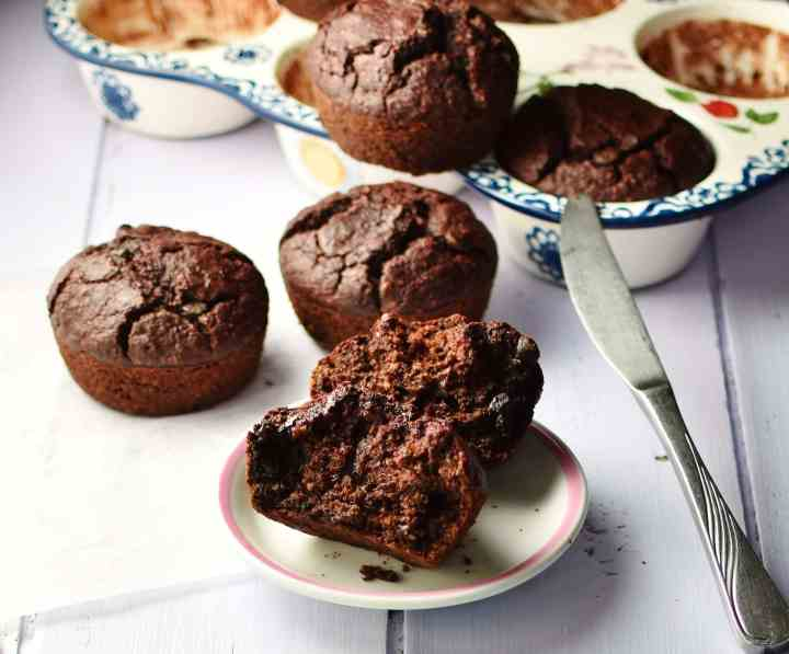 Side view of halved chocolate muffin on top of small white plate, with more muffins behind and inside ceramic muffin pan, with knife, in background.