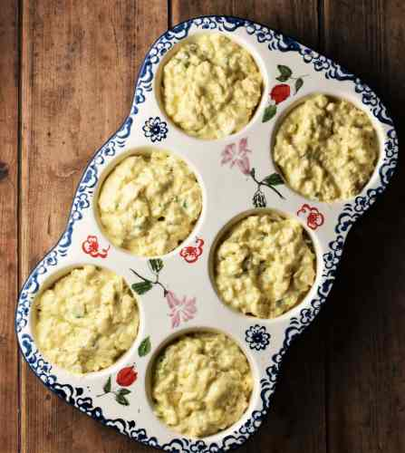 Lumpy batter in 6-hole white ceramic muffin pan with flowery blue pattern.