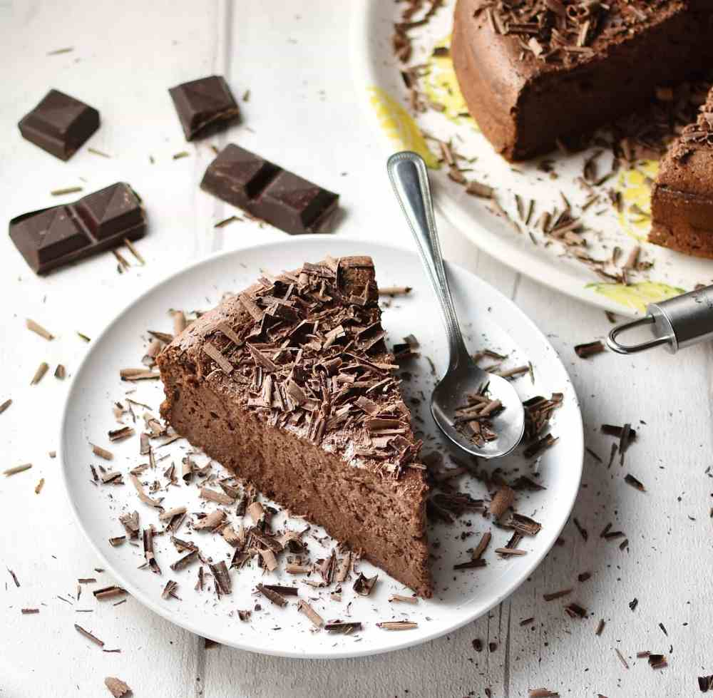 Chocolate cheesecake slice with spoon on top of white plate, with chocolate pieces and partial view of chocolate cake in background.