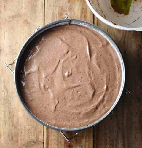 Chocolate cheesecake batter in round cake pan.