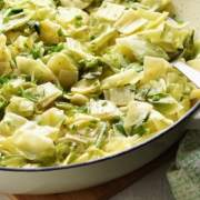 Partial view of Polish pasta with chopped cabbage in large white, round dish.