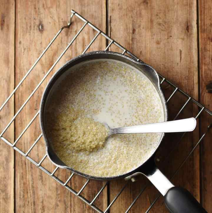 Quinoa with milk in saucepan with spoon.