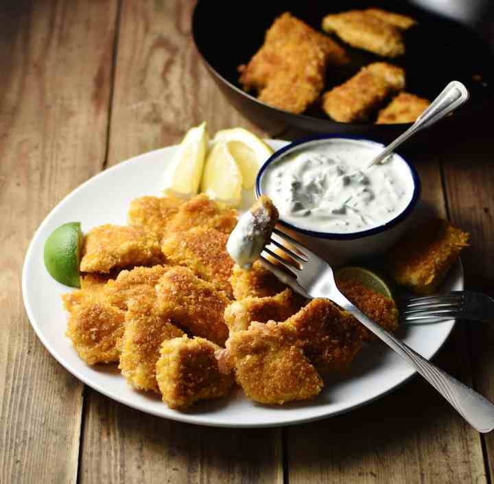 Chicken nuggets with fork, lemon and lime wedges, and yogurt dip in small dish with spoon on top of white plate, with chicken nuggets in skillet in background.