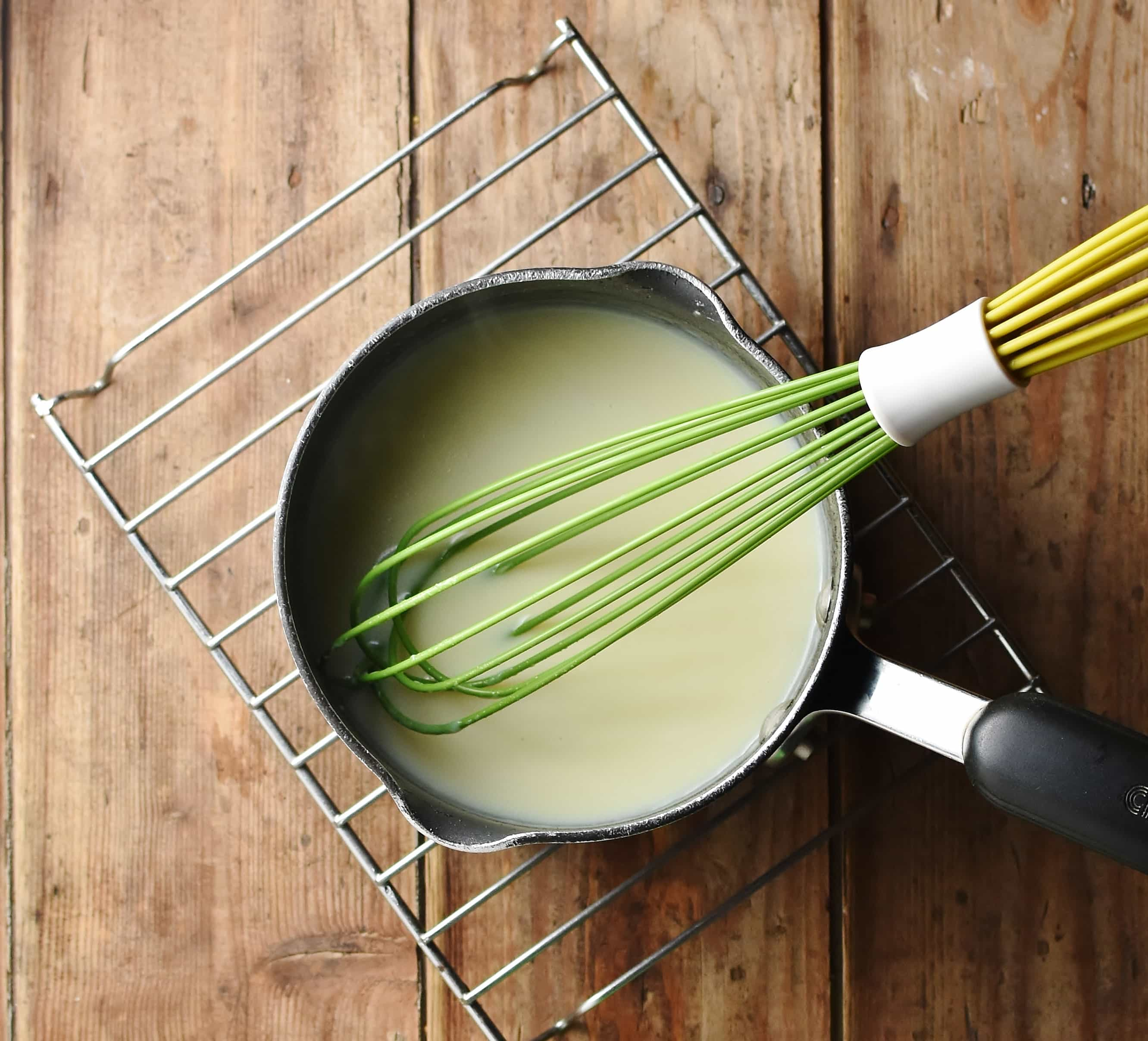 White sauce with green whisk in saucepan on top of rack.