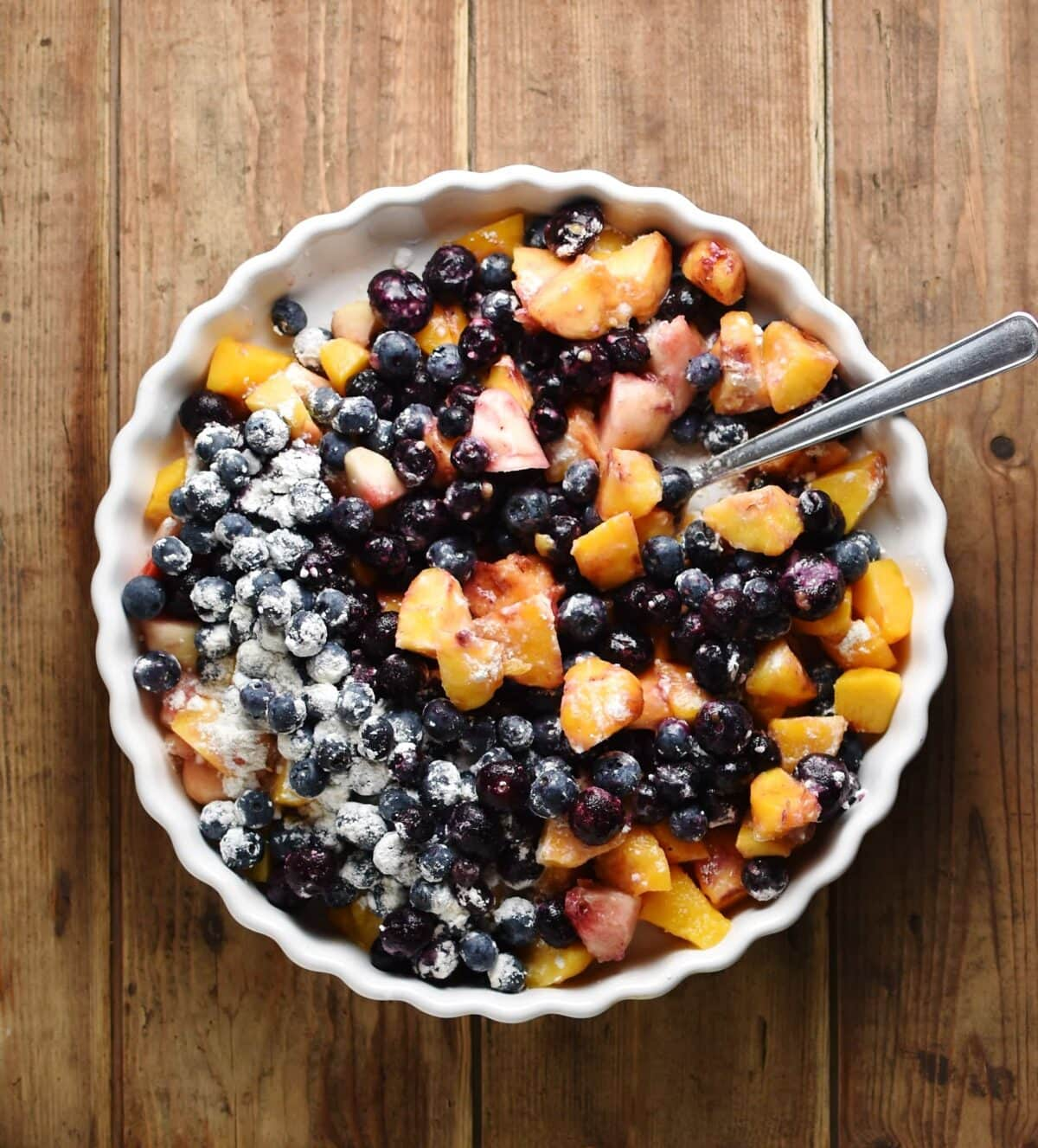 Top down view of cubed peaches and blueberries with flour and spoon in white pie dish.