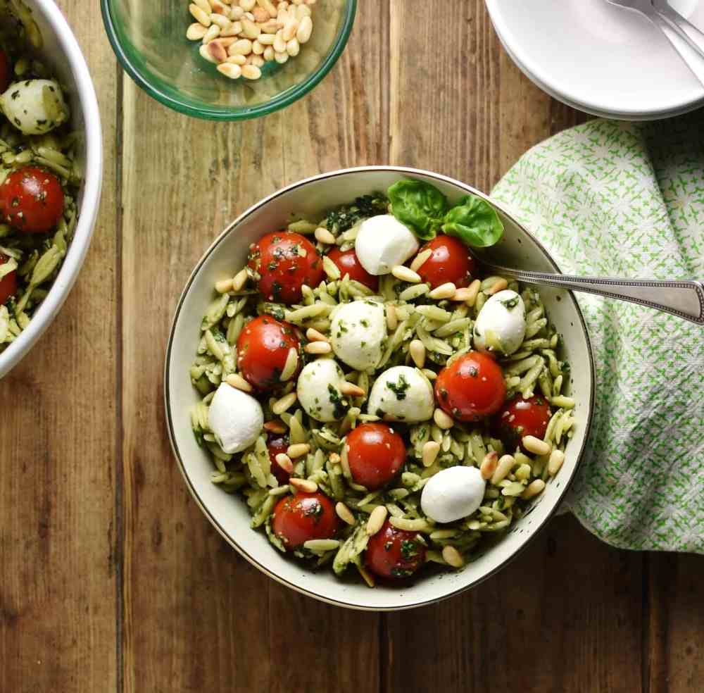 Top down view of orzo pesto pasta with cherry tomatoes, mini mozzarellas and spoon inside green bowl wrapped in green cloth, with white bowl and pine nuts in small dish in background.