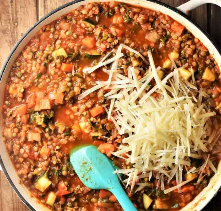 Lentil and vegetable lasagne filling with grated cheese in large pan.