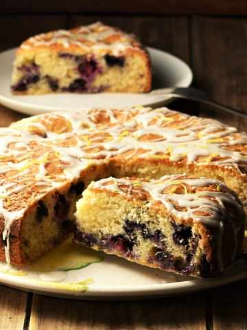 Side view of blueberry cake with slice on top of plate.