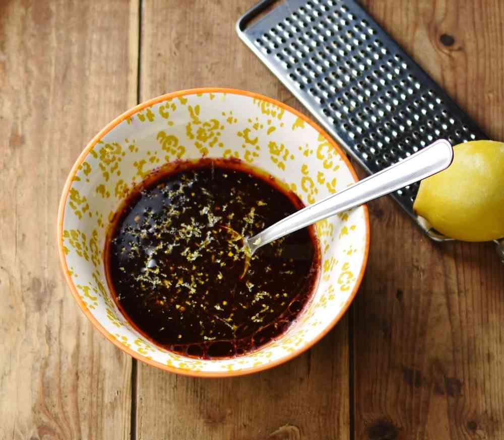Blueberry vinaigrette ingredients with spoon in yellow-and-white patterned bowl, with lemon and zester in top right corner.