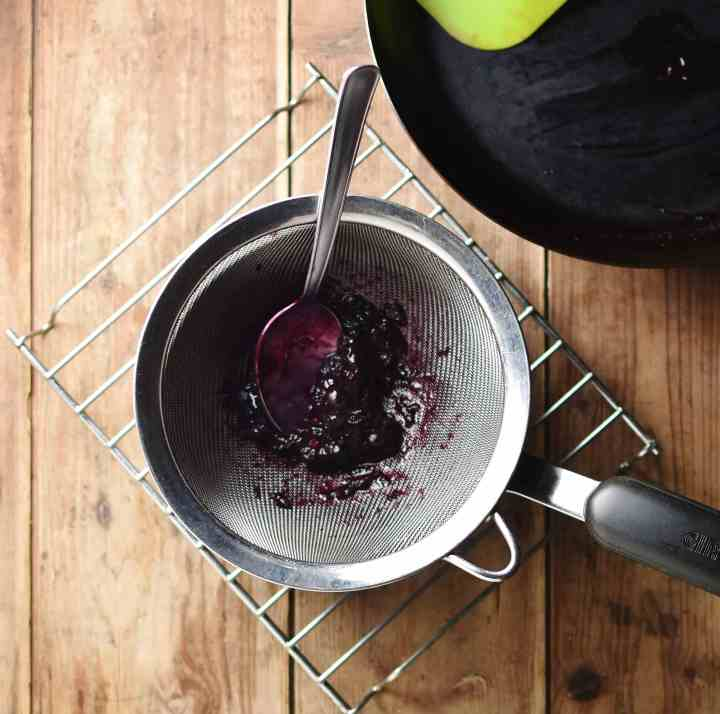Blueberry pulp with spoon inside sieve on top of saucepan on cooling rack, with pan in top right corner,
