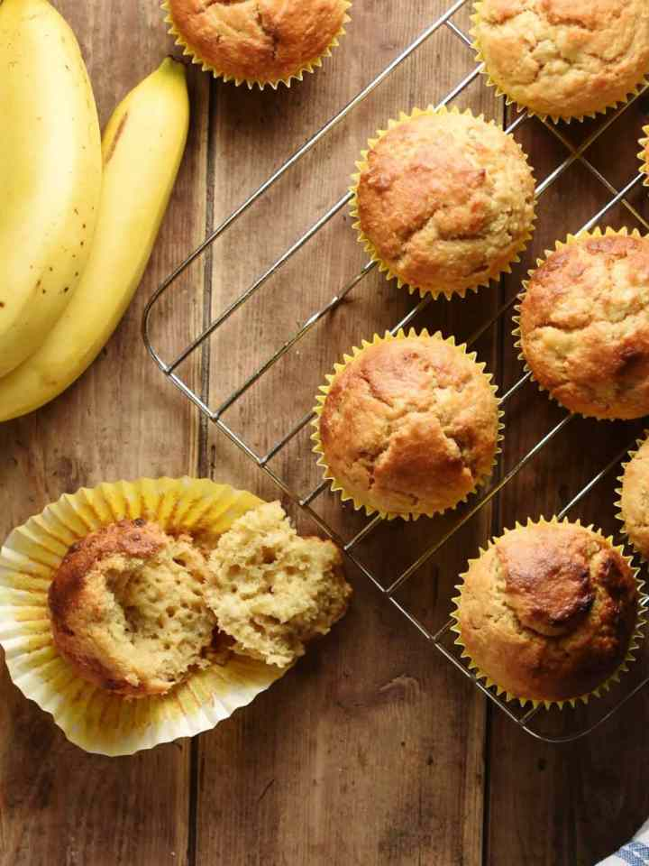 Top down view of banana muffins in yellow cases on top of cooling rack and bananas in top left corner.