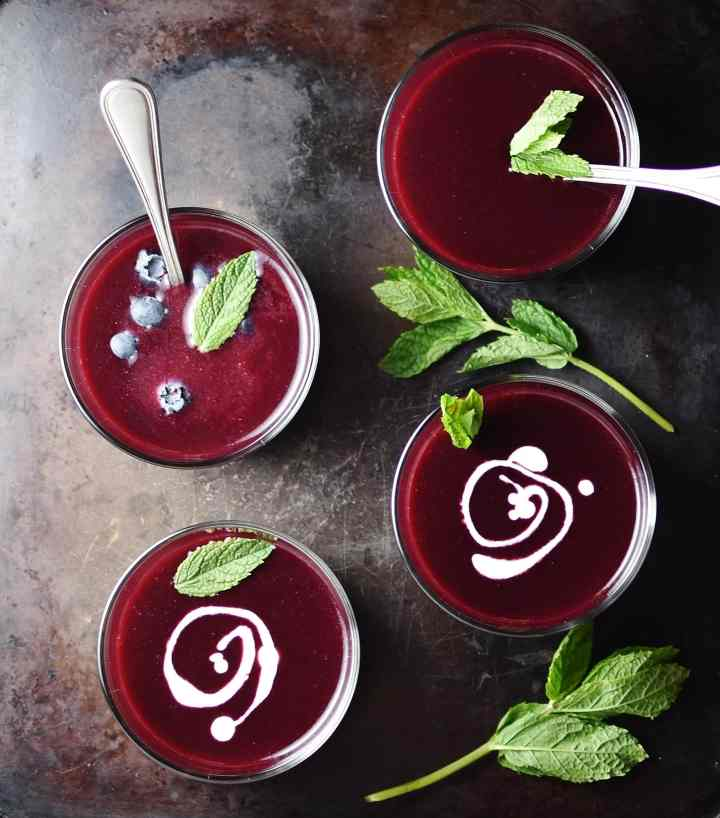 Top down view of fruit soup in 4 glasses with 2 spoons, mint leaves and swirls of cream on top of dark surface.