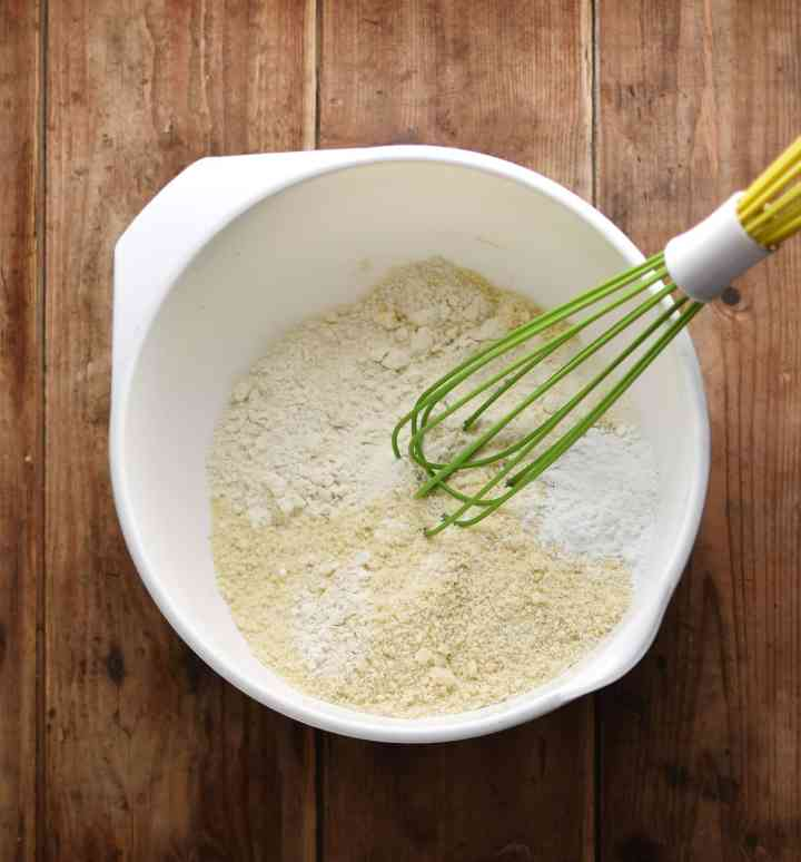 Dry muffin ingredients with whisk in white bowl.