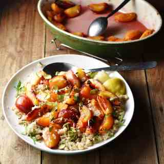 Peaches and quinoa with lemon wedges, nuts, herbs and large spoon on top of white plate, with green oval dish with cooked peaches and juices in background.