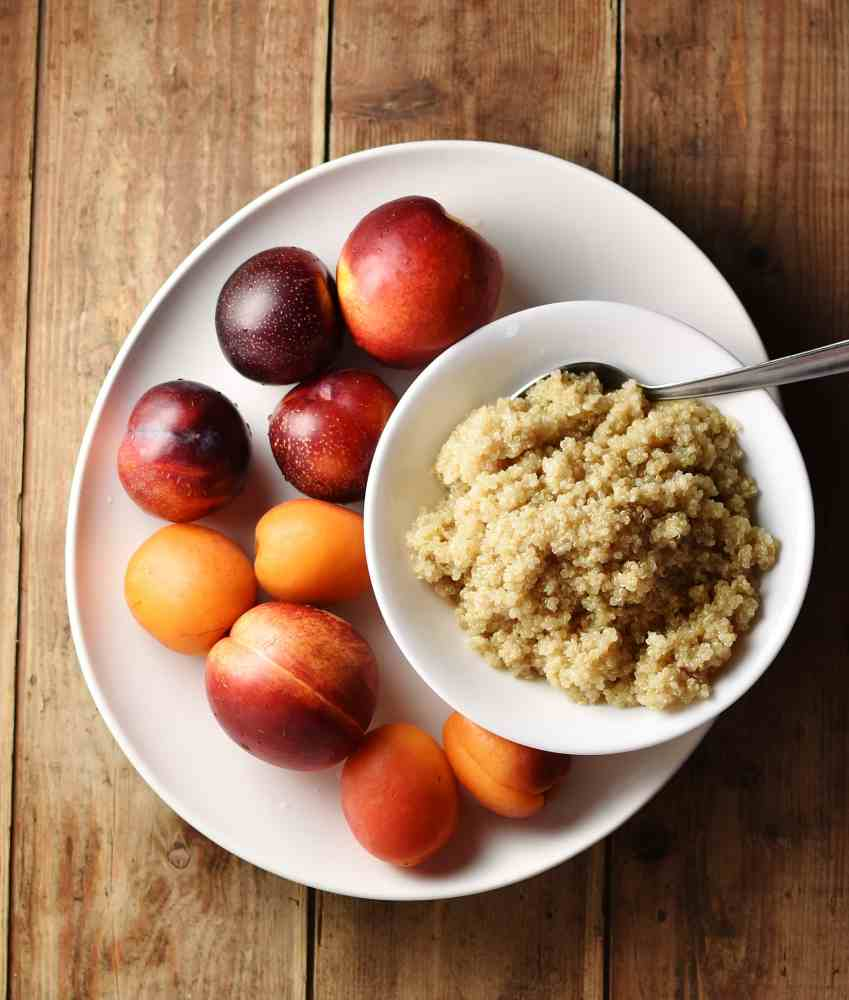 Nectarines, plums and apricots and cooked quinoa inside white bowl with spoon on top of large white plate.