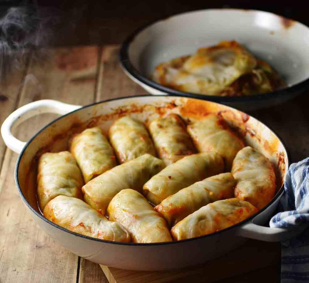 Side view of cabbage rolls in white dish with lid in background.