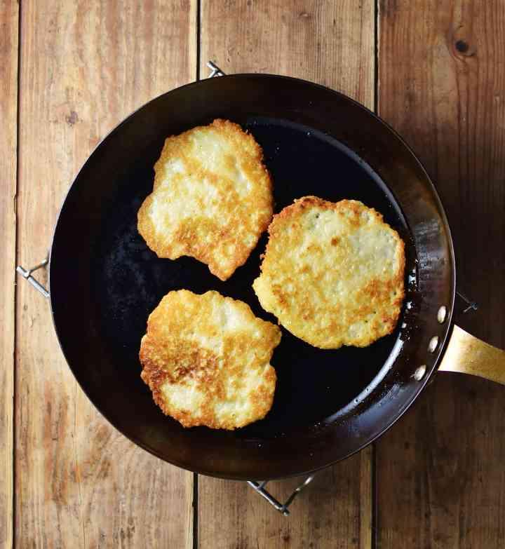3 crispy pancakes in skillet.