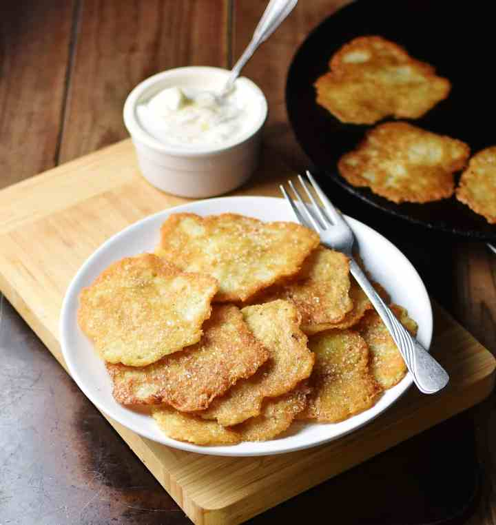 Potato pancakes with fork on top of white plate with yogurt in white dish with spoon and more pancakes in skillet in background.
