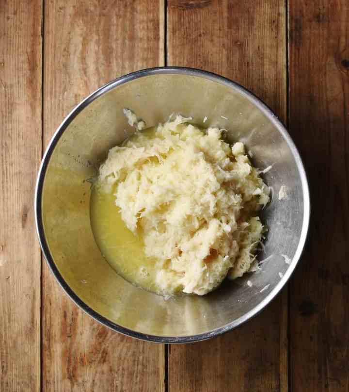 Grated potato mixture in metal bowl.