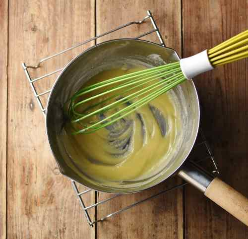 Roux inside saucepan with green whisk on top of cooling rack.
