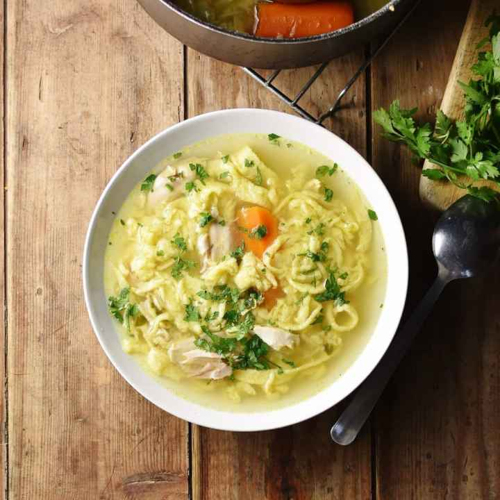 Chicken noodle soup in white bowl with spoon and parsley to right and partial view of pot at the top.
