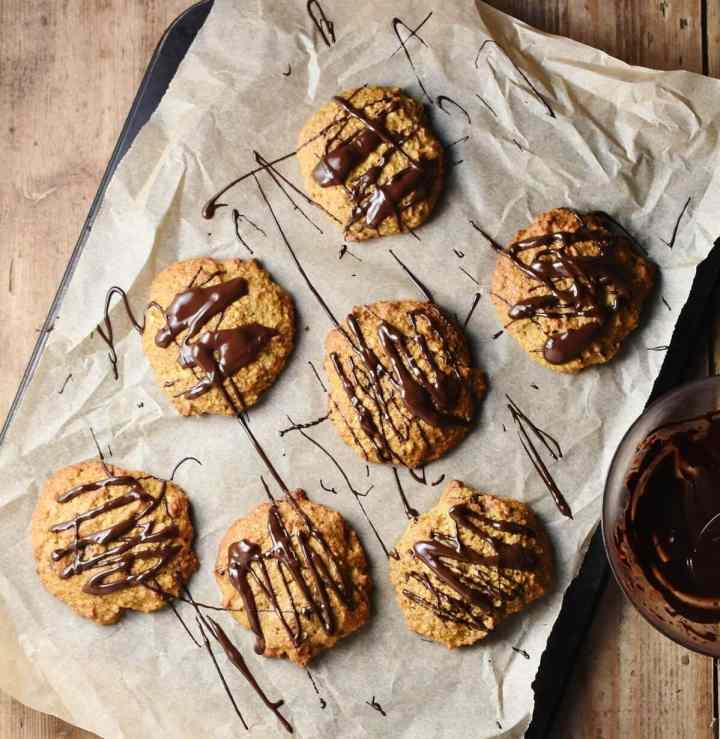 Pumpkin cookies with chocolate drizzle on top of paper.