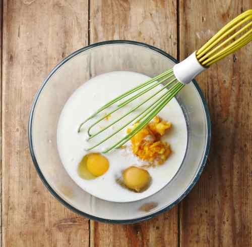2 eggs, milk and pumpkin puree in metal bowl with green whisk.