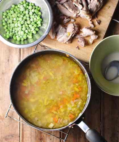 Chicken vegetable soup in large pot, with flour mixture in dish, chicken pieces on wooden board and frozen peas in bowl in background.
