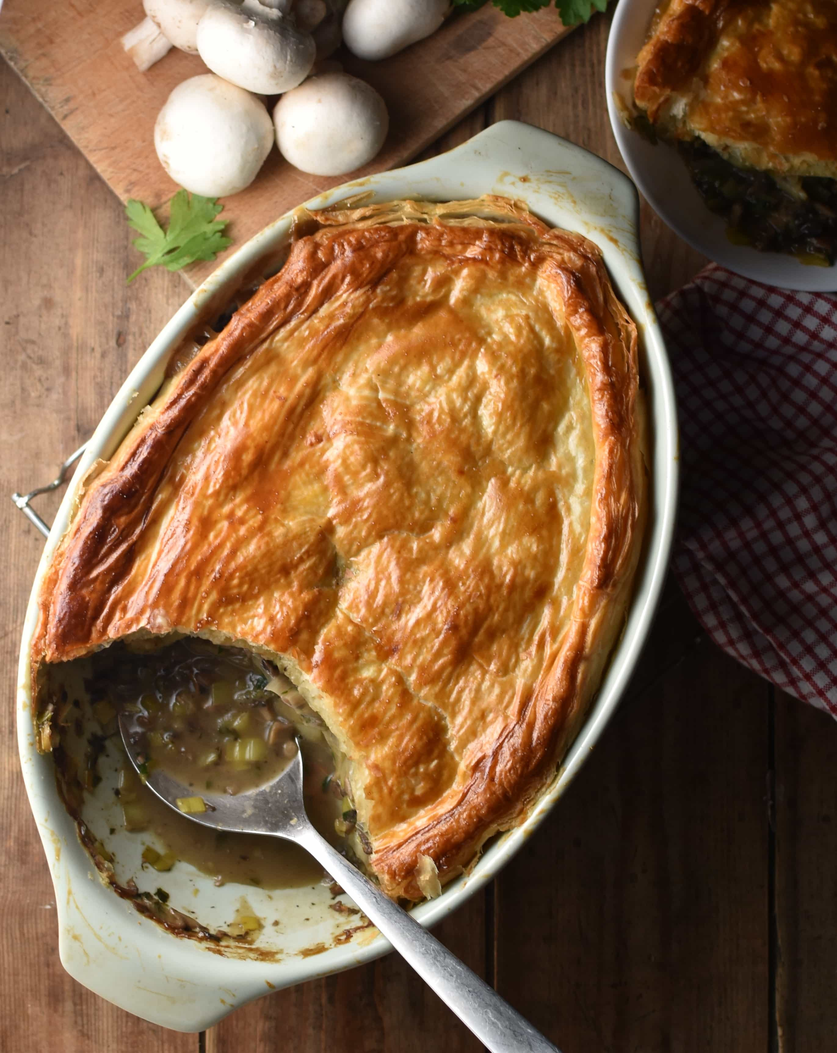 Mushroom and leek pie topped with golden brown pastry in white oval dish with spoon, mushrooms and pie in white dish in background.