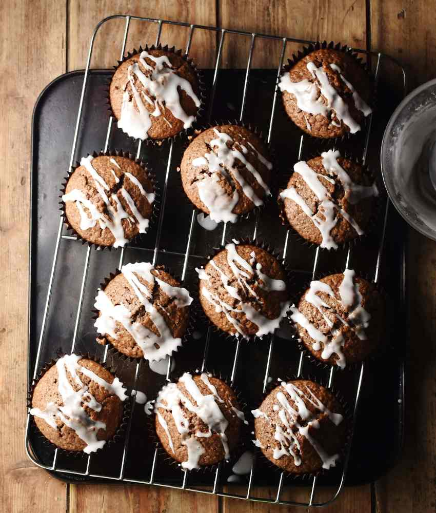 11 gingerbread muffins with icing on top of rack and tray.