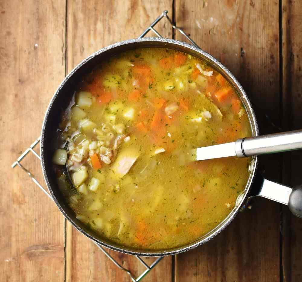 Krupnik soup in large pot with ladle.