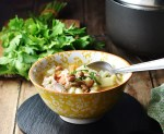 Side view of chunky turkey vegetable soup in yellow bowl with spoon, and fresh parsley bunch and pot in background.