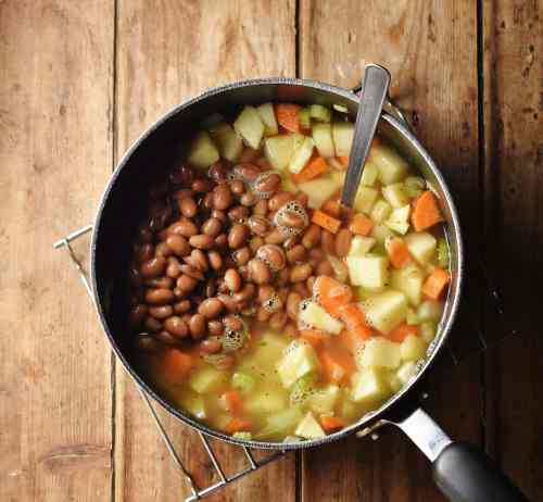 Cubed vegetables and beans in large pot with spoon.