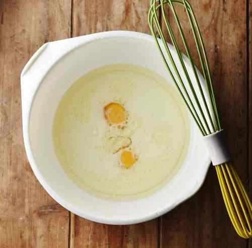2 egg yolks and milk in large white bowl with green whisk.