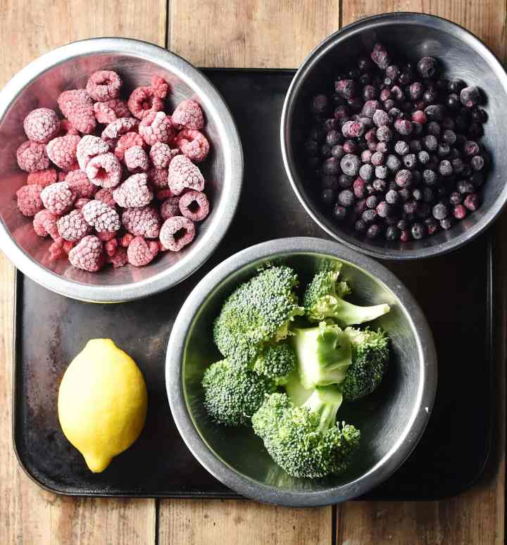 Frozen blueberries, raspberries and chopped broccoli in individual metal bowls and lemon on top of black tray.