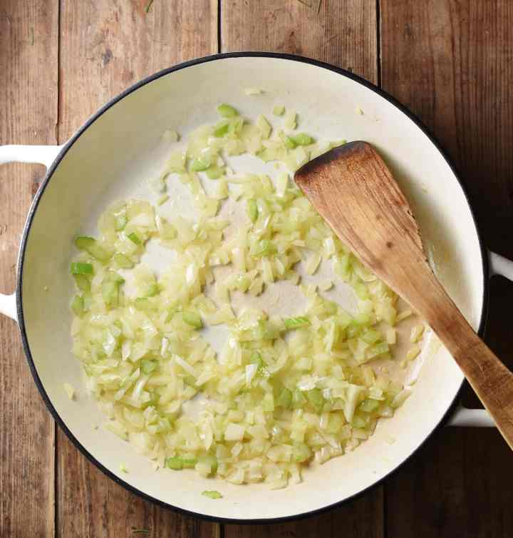 Chopped onions and celery in large white shallow dish with wooden spatula.