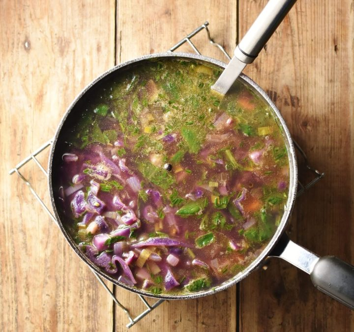 Red vegetable soup with herbs in large pot with ladle on top of rack.