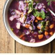 Chunky red cabbage soup in bowl with herbs in background.