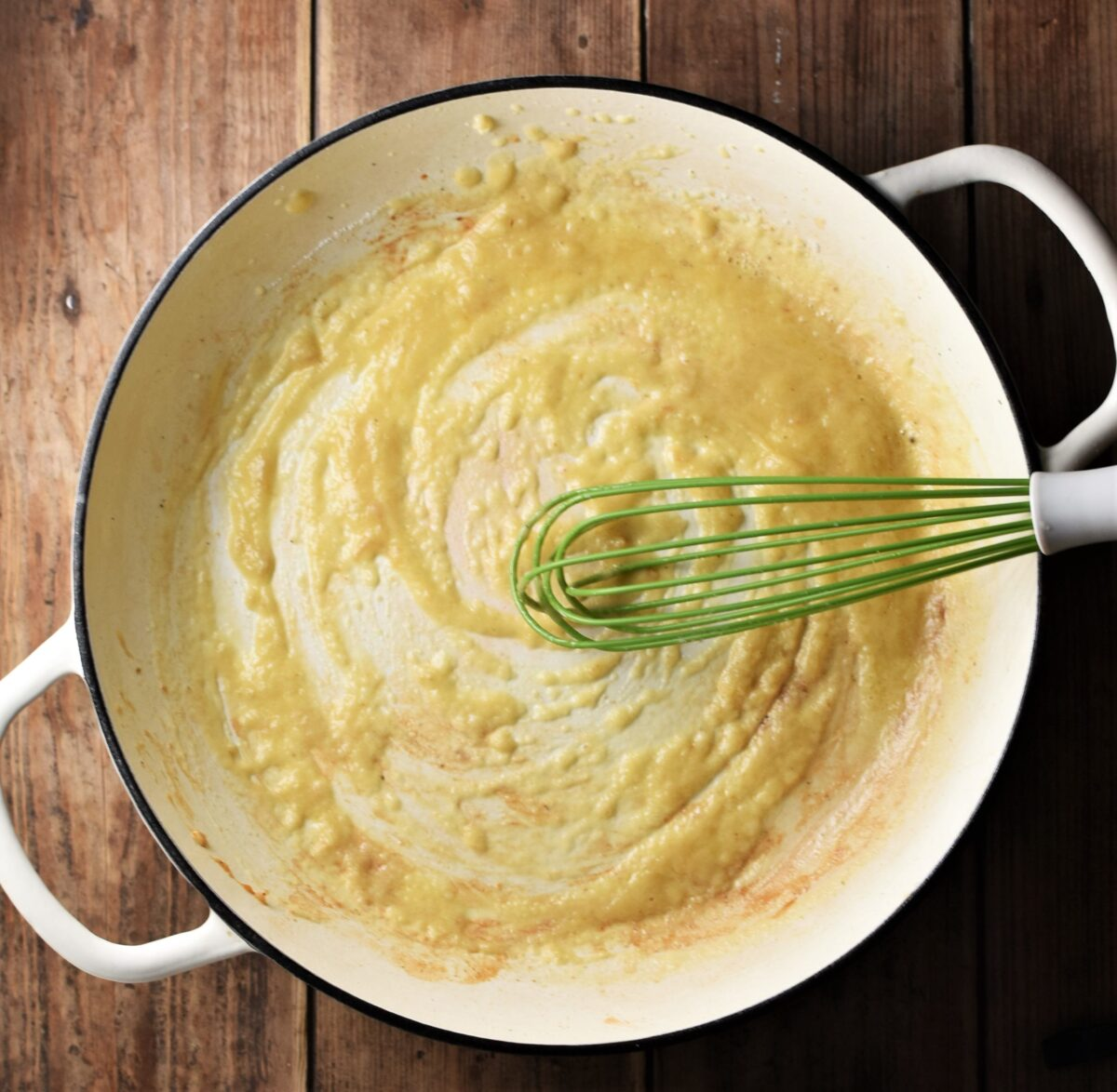 Top down view of roux in large shallow white pan with green whisk.