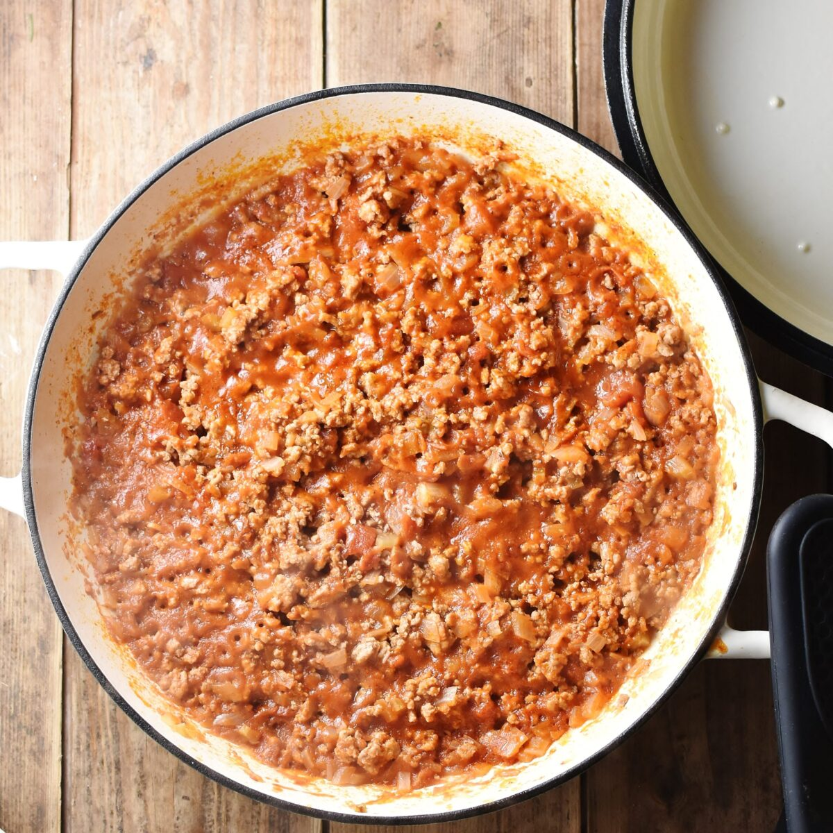 Thick tomato meat sauce in large shallow white pan, with white lid in top right corner.