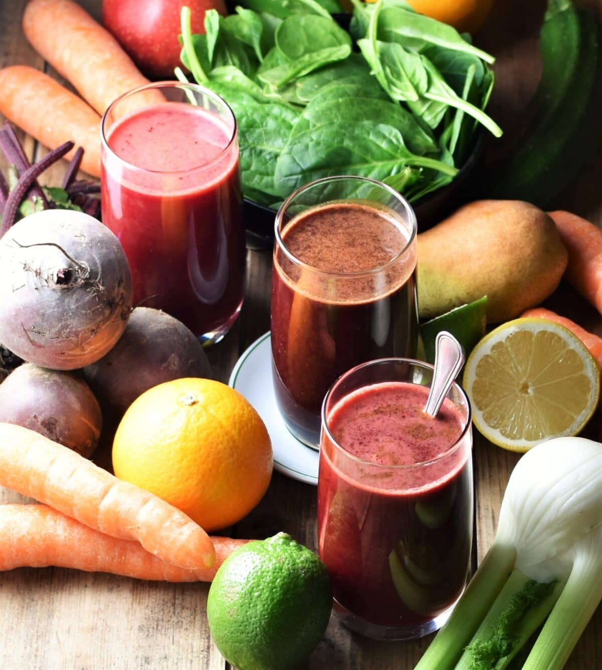 3 glasses with dark juice surrounded by fresh fruits and vegetables.
