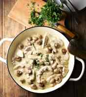 Creamy turkey and mushroom in large white pan, with chopped herbs on top of wooden board with knife in background.