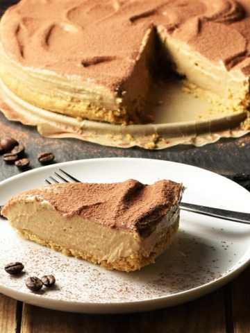 Side view of coffee cheesecake slice on white plate with fork and coffee beans, with cheesecake and spatula in background.