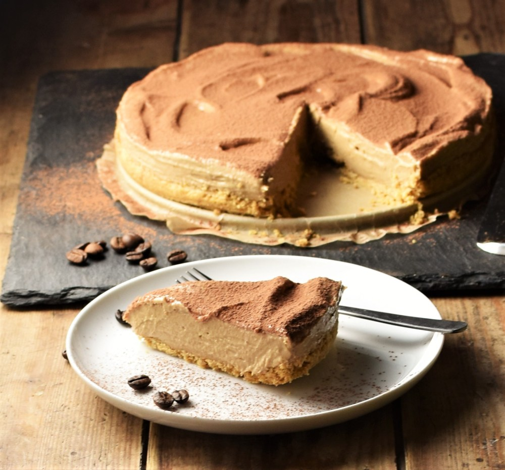 Side view of cheesecake slice on white plate with coffee beans and fork, with cheesecake in background.