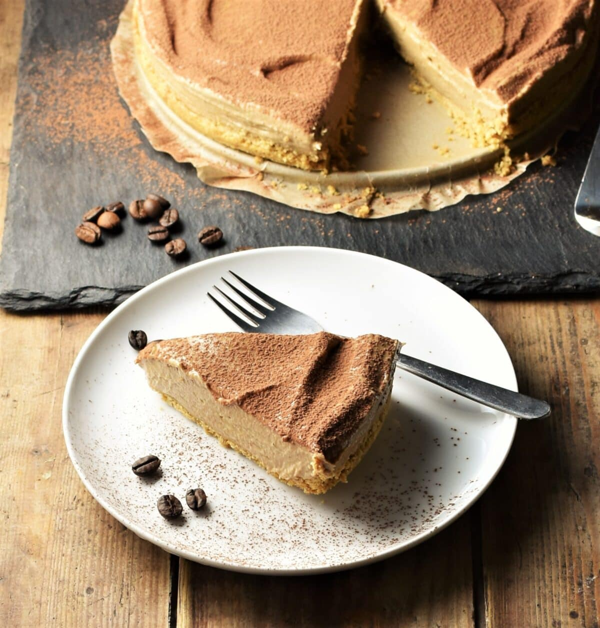 Slice of coffee cheesecake on white plate with coffee beans and fork, with cheesecake in background.