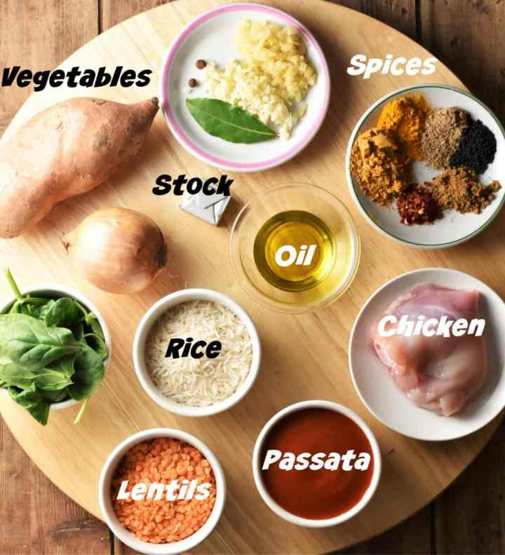 Mulligatawny soup ingredients in small dishes on top of round wooden board.