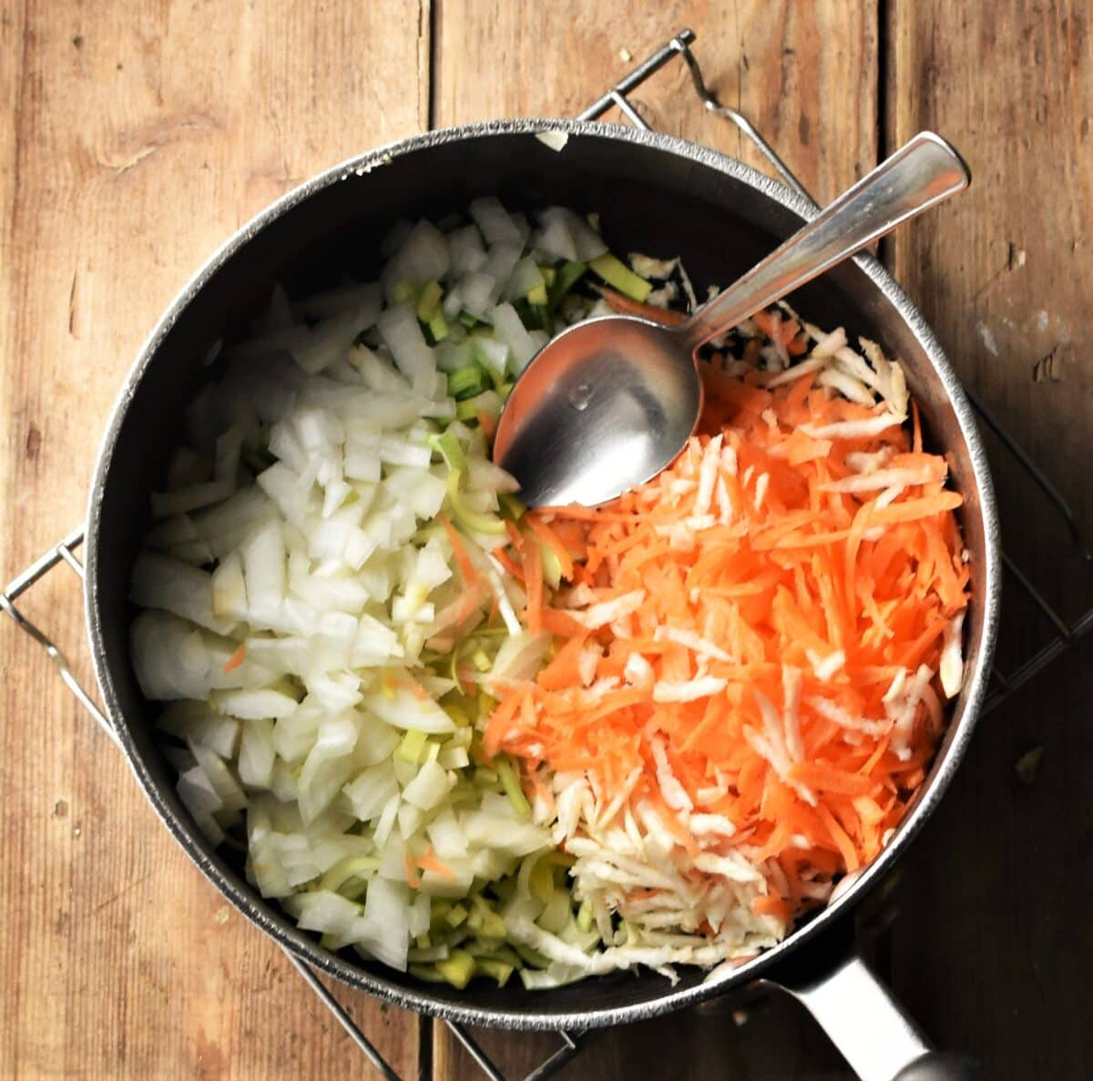 Chopped onion and grated vegetables in large pot with spoon.