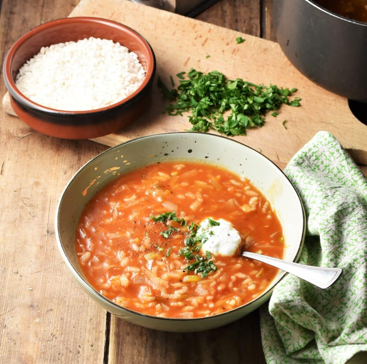 Chunky rice tomato soup with yogurt and herbs in green bowl with spoon, green cloth to the right, rice in brown dish and chopped herbs on wooden board in background.